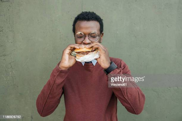 young man eating cheeseburger, with eyes closed - burger stock pictures, royalty-free photos & images