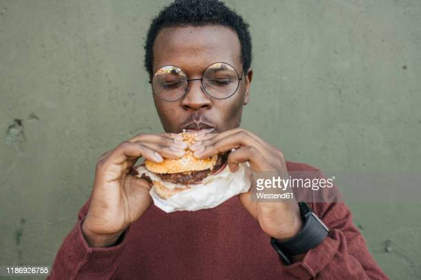 young man eating cheeseburger, with eyes closed - biting stock pictures, royalty-free photos & images