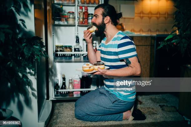 Young man eating donuts in front of the refrigerator late night
