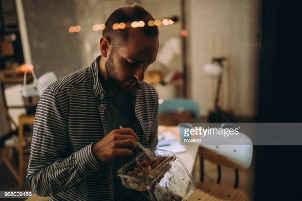 Junger Mann Essen Fastfood im Büro