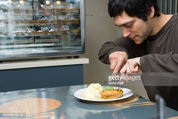 Young man eating food in cafe