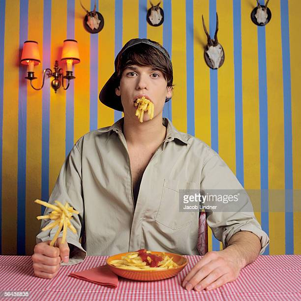 young man eating french fries - fries stock-fotos und bilder