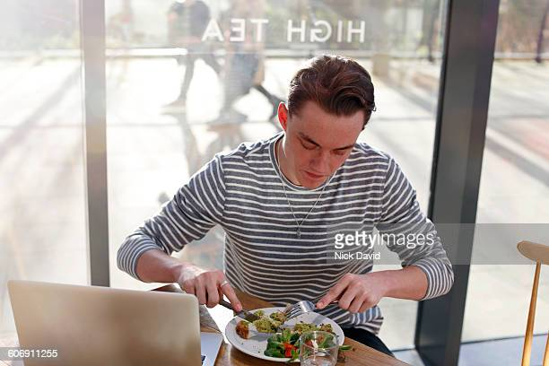 young man eating in a cafe