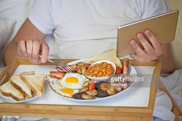 Young man eating Irish breakfast & looking up social media on tablet