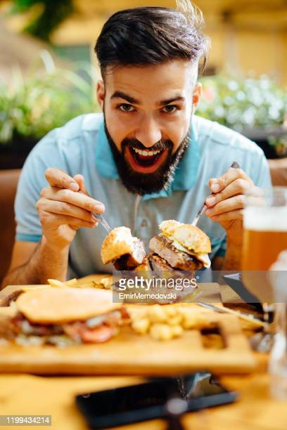 young man eating oversized burger in a fast food restaurant - só um homem imagens e fotografias de stock