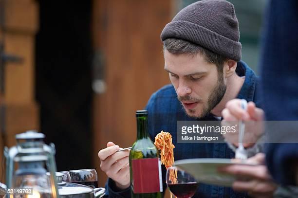 Young man eating pasta during glamping holiday.