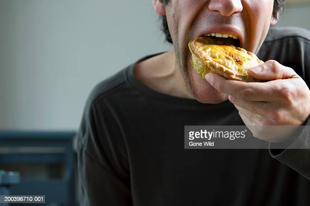 Young man eating pie, close-up