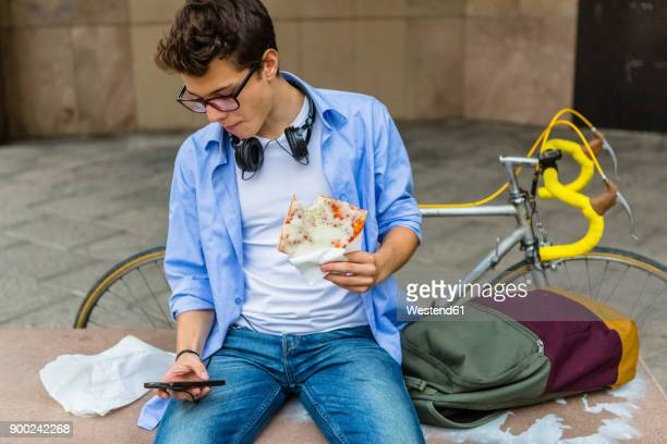 young man eating pizza on a bench while looking at cell phone - one man only stock pictures, royalty-free photos & images