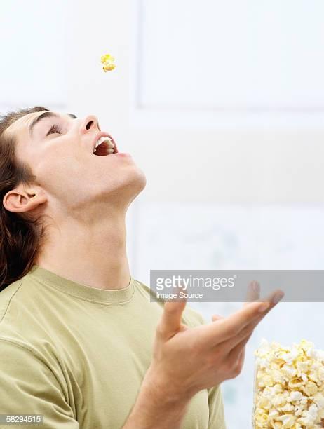 Young man eating popcorn