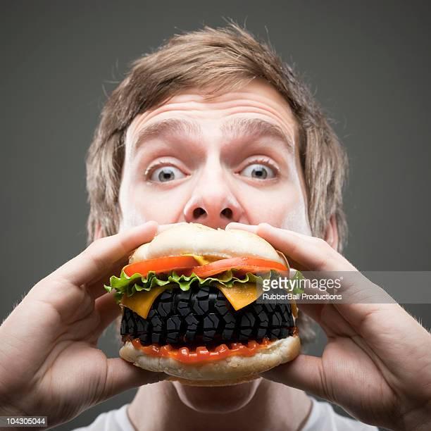 Young man eating tire burger,studio shot