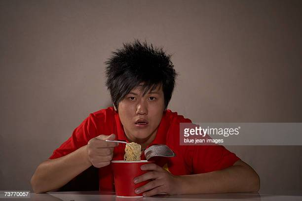 A young man eats instant noodles while watching a movie looking into the camera.