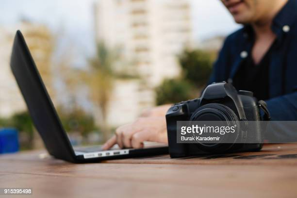 Young man editing photos on location