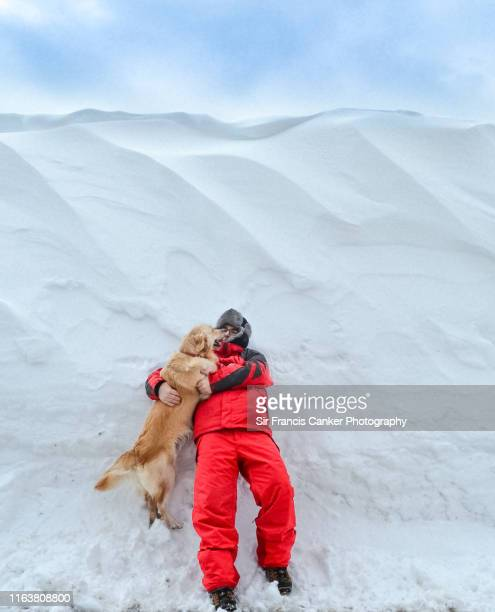 young man embracing a purebred female golden retriever in the snow - クールマイヨール ストックフォトと画像