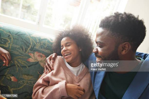 young man embracing cheerful teenage girl on sofa - sister stock pictures, royalty-free photos & images
