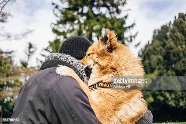Young man embracing Eurasier at park