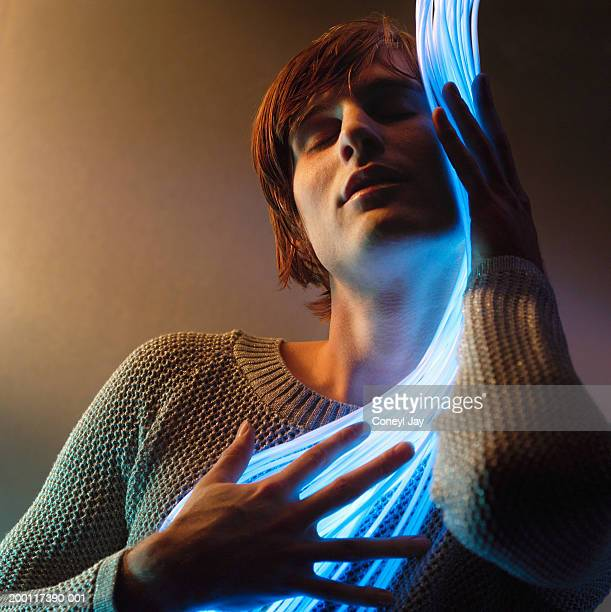 Young man embracing fibre optic cables, eyes closed