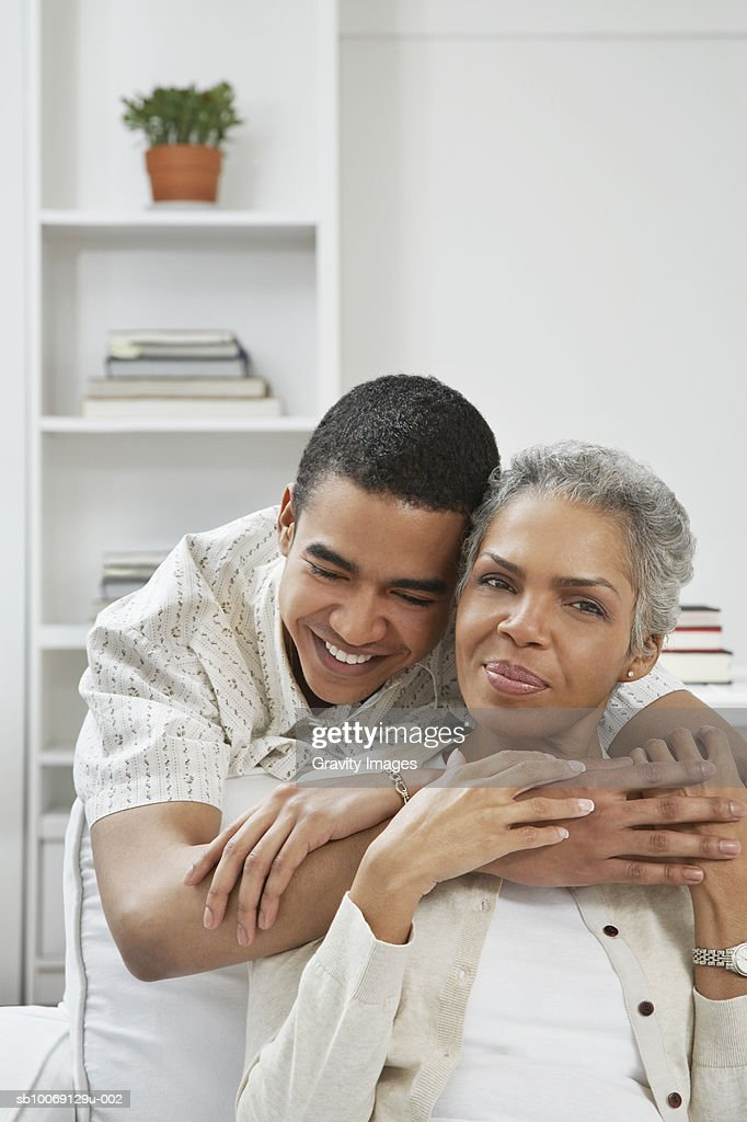 Young man embracing mother, smiling : Stockfoto