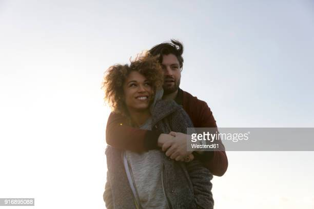 Young man embracing smiling girlfriend outdoors