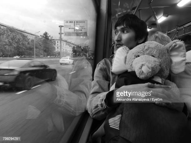 Young Man Embracing Stuffed Elephant While Looking Through Window Of Bus
