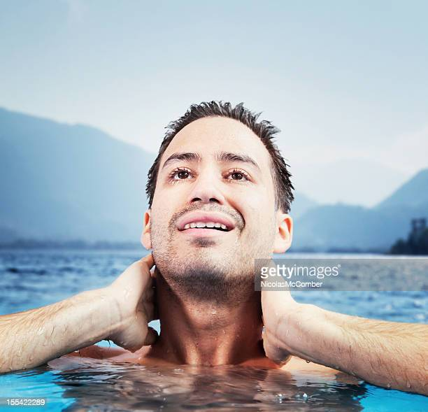 Young man emerges from a lake swim