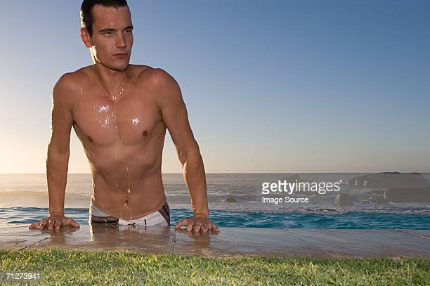 Young man emerging from pool
