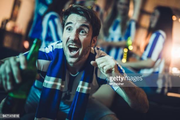 young man encouraging his team while watching a match on tv at home. - marcar golo imagens e fotografias de stock