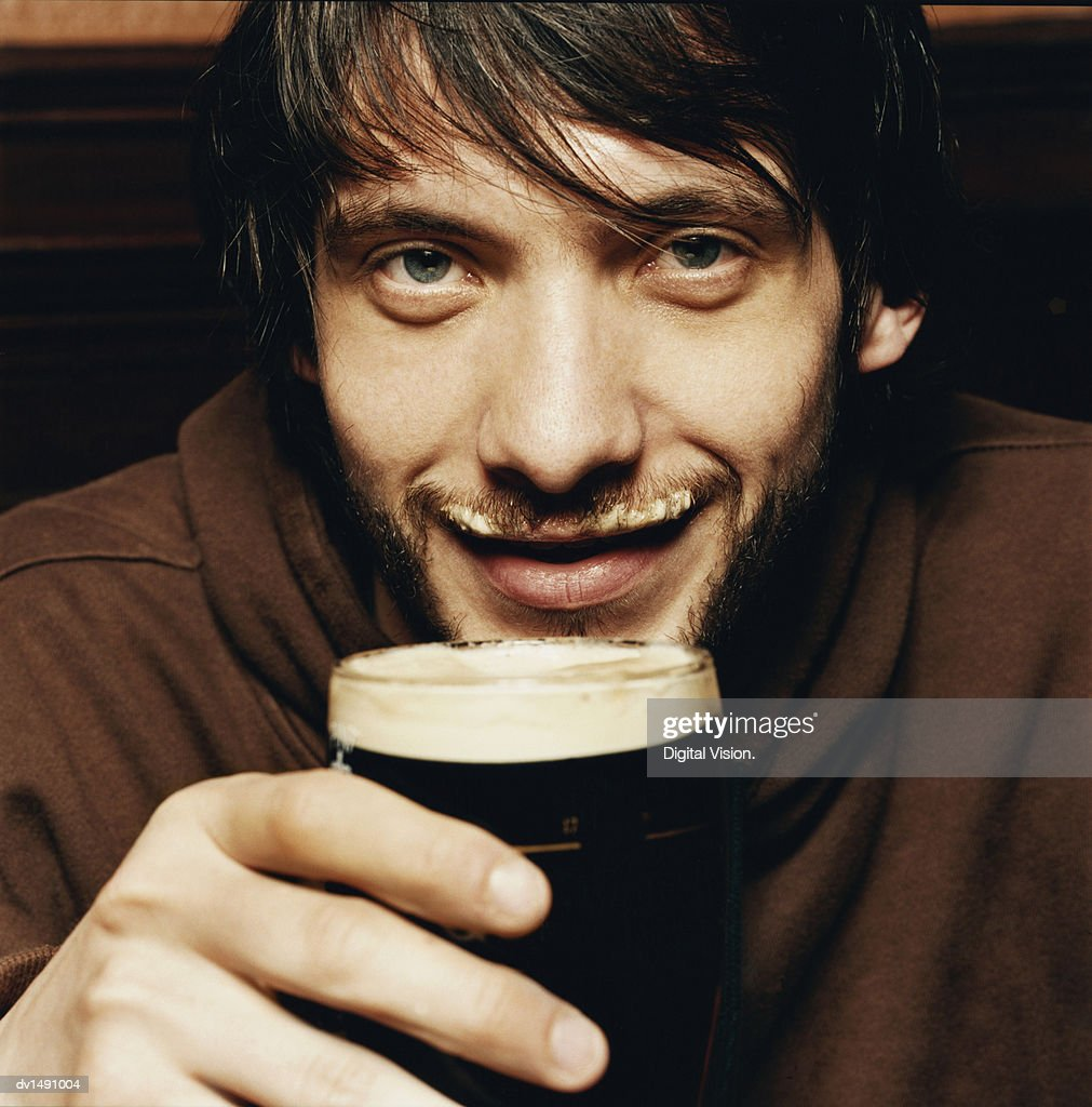 Young Man Enjoying a Drink of Stout in a Pub : Stock Photo