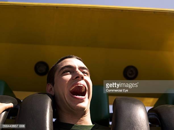 Young man enjoying amusement park ride, close-up