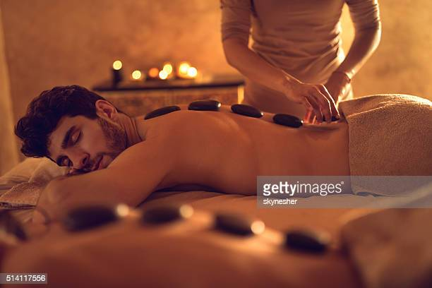 Young man enjoying during hot stone therapy at the spa.