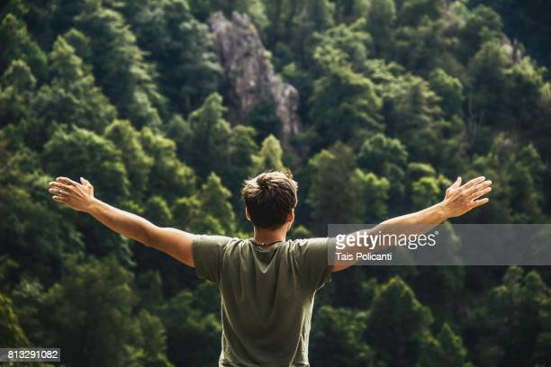 A young man enjoying freedom after hiking at the Bodetal valley in Thale - Harz mountains, Thale, Saxony-Anhalt, Germany