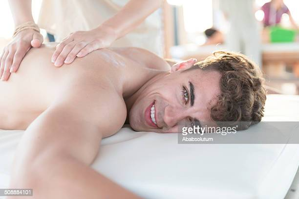 young man enjoying massage at spa outdoors, mediterranean, europe - body massage stock photos and pictures
