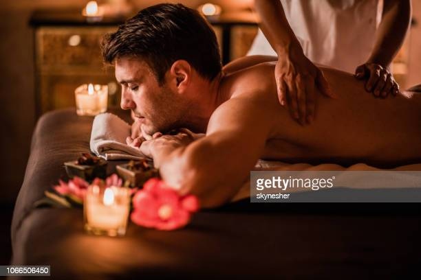 young man enjoying on a massage treatment at the spa. - massage stock pictures, royalty-free photos & images