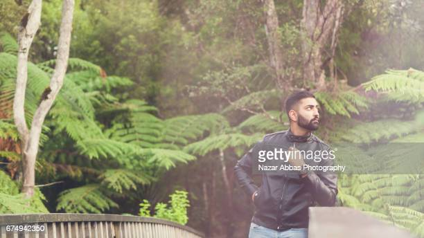 young man enjoying outdoors during a walk in bush reserve auckland, new zealand. - handsome pakistani men - fotografias e filmes do acervo