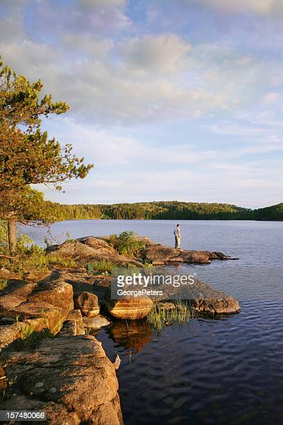 young man enjoying serene moment on wilderness lake - boundary waters canoe area stock pictures, royalty-free photos & images