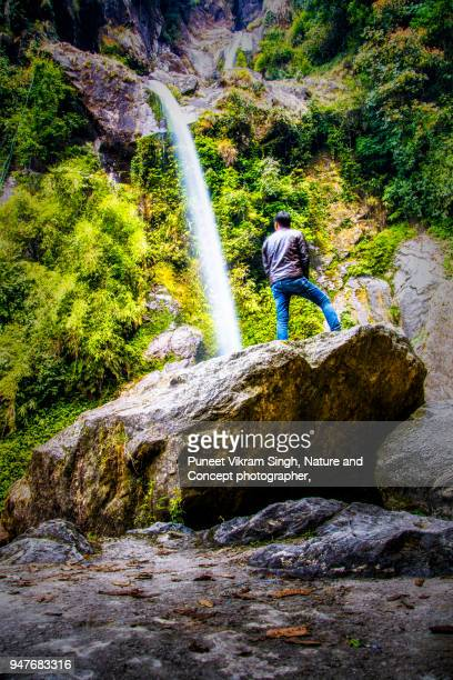 a young man enjoying the natural beauty of seven sisters waterfall - northeast india stock photos and pictures