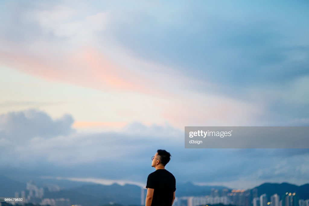 Young man enjoying the tranquility while gazing at dramatic sky in deep thought : Stock Photo