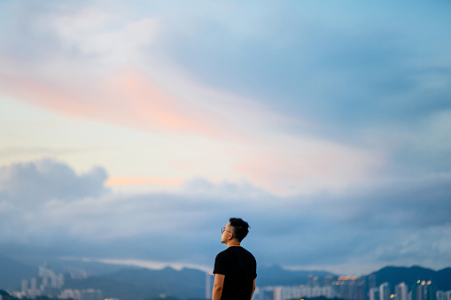Young man enjoying the tranquility while gazing at dramatic sky in deep thought - gettyimageskorea