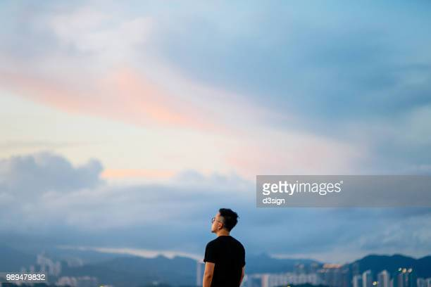 young man enjoying the tranquility while gazing at dramatic sky in deep thought - libertad fotografías e imágenes de stock