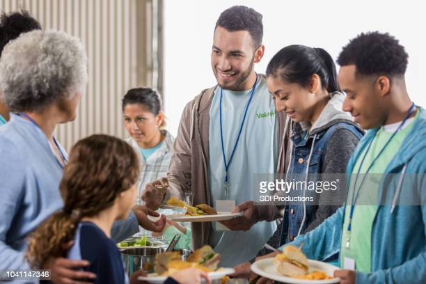 young man enjoys serving meals at soup kitchen - community centre stock pictures, royalty-free photos & images