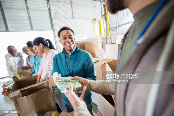 young man enjoys working at local food bank. - african american man helping elderly stock pictures, royalty-free photos & images