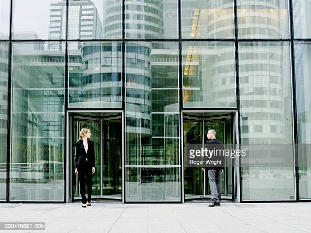 Young man entering building as young woman exits