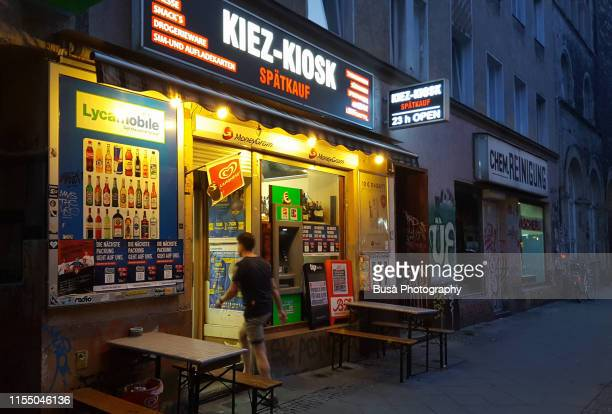 young man entering grocery store in the kreuzberg district of berlin at night. berlin, germany - one night stand stock-fotos und bilder