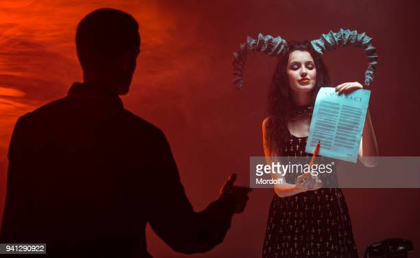 young man enters into contract with female devil - devil stock pictures, royalty-free photos & images