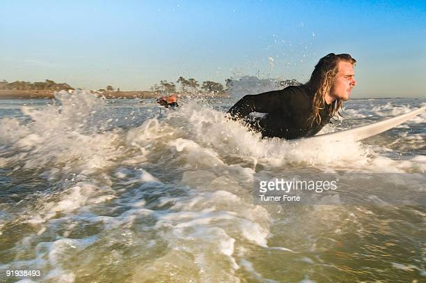 Young man enters ocean surf