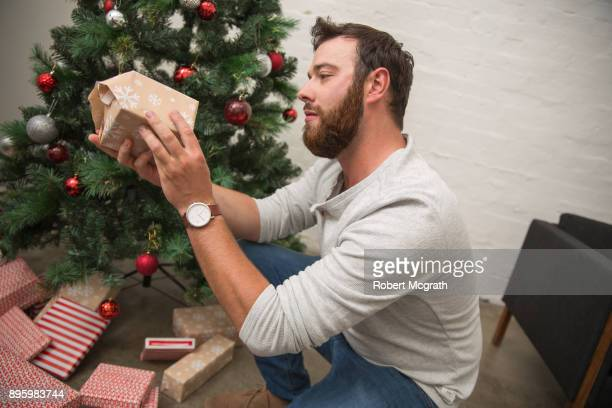 Young man examines Christmas presents round the tree on Christmas morning.