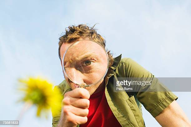 Young man examining dandelion with magnifying glass, low angle view