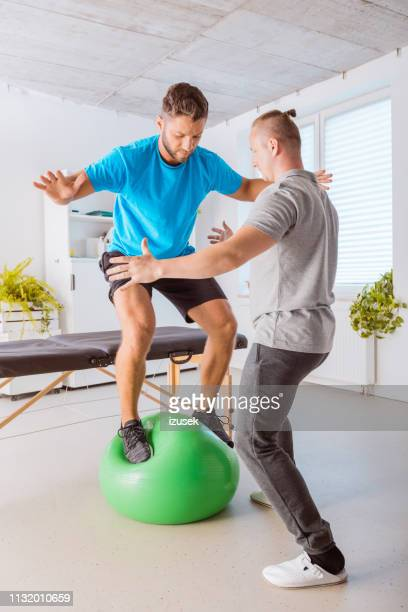 young man excercising on ball with his physiotherapist on ball - sports medicine stock pictures, royalty-free photos & images