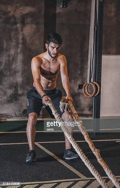Young Man Excerising With Ropes