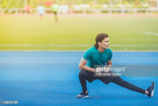young man exercising at stadium - legs apart stock pictures, royalty-free photos & images