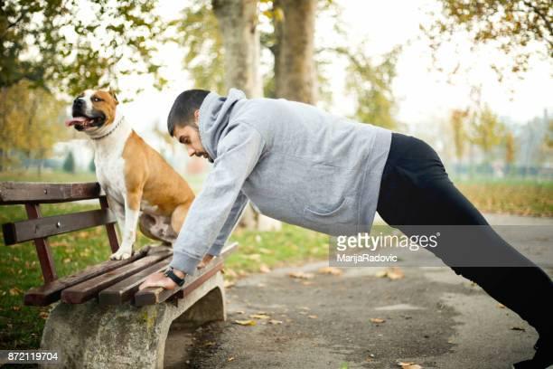 Jeune homme exerçant dans un parc avec son chien